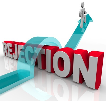 8989826 - a person jumps over the word rejection, riding an arrow to success